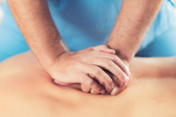 Chiropractic - doctor placing hands on patients back