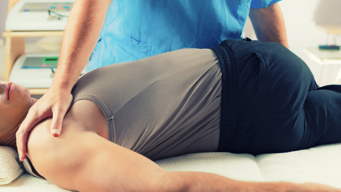 Chiropractic - doctor helping patient stretch back