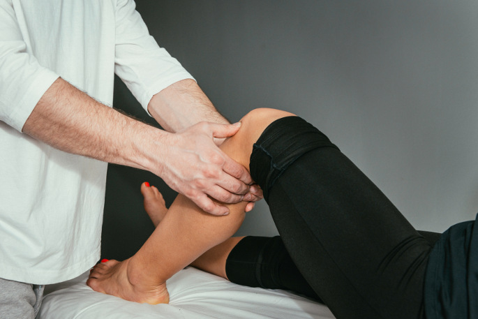 Physical Therapy Treatment - doctor performing physical therapy on patients leg