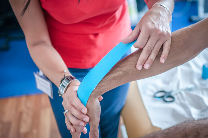 Physical Therapy Treatment - doctor performing physical therapy on patients wrist and arm